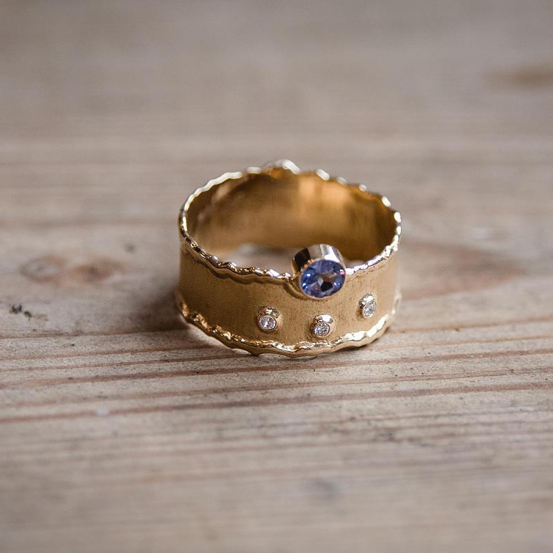 Ring aus 585 Gelbgold (14k) mit angeschmolzenen Rändern (flambiert), 3 Brillanten und einem facettierten Tansanit (Zoisit)